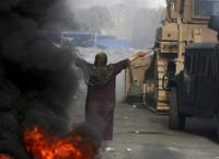 Египтянка пытается остановить военный бульдозер во время акций протеста в Египте