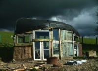 Дом из окон и дверей с лодкой вместо крыши