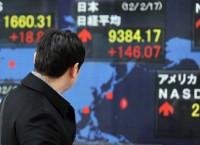 Прохожий рассматривает цены на акции на электронном табло в Токио
